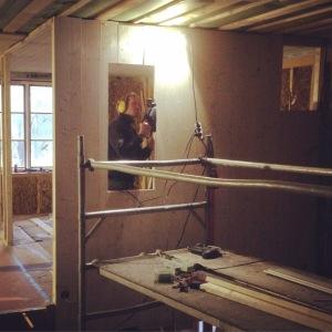 Våra överblivna golvplank i gran hamnar på väggen. Jon är med och hjälper oss.
